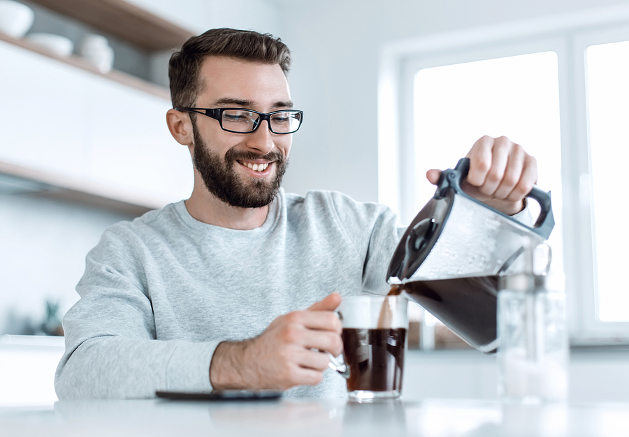 Man pouring himself black coffee